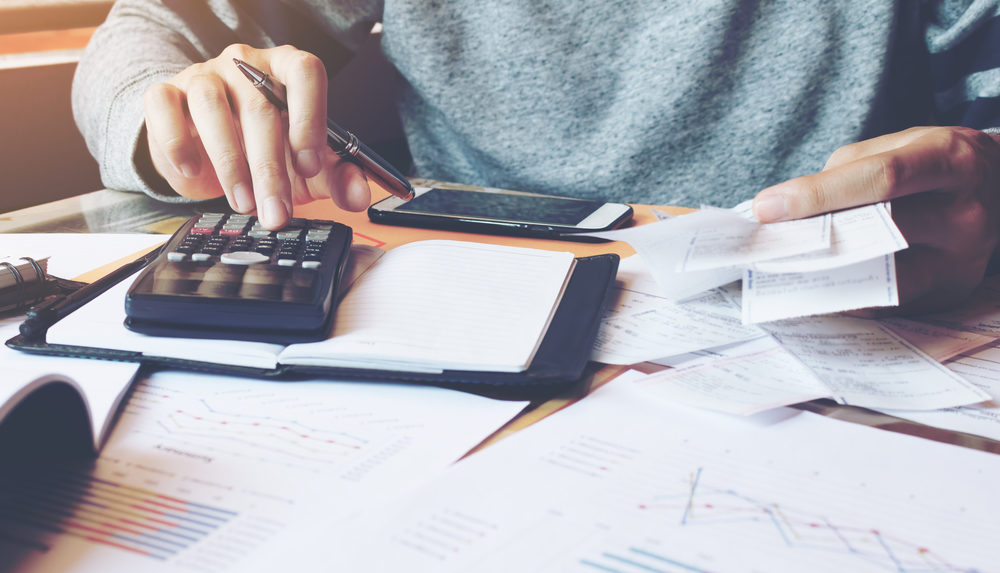 person computing expenses with a calculator | Rogson Firm | Business Litigation Attorney